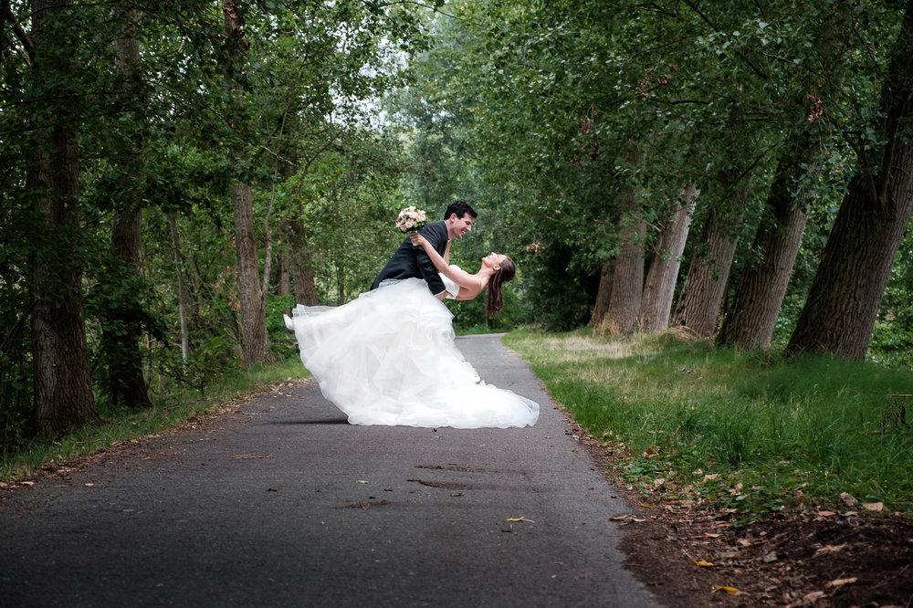 Sofie en Bernard hadden het privilege om in de tuin van de ouders van de bruidegom hun trouwfeest te houden. Geen slecht idee, zo bleek. De huwelijksfotografen van iso800 waren gelukkige getuigen. Foto van het paar tijdens de shoot in een bos, oefenende voor de openingsdans.
