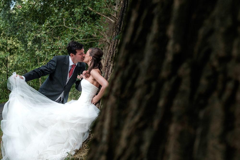 Sofie en Bernard hadden het privilege om in de tuin van de ouders van de bruidegom hun trouwfeest te houden. Geen slecht idee, zo bleek. De huwelijksfotografen van iso800 waren gelukkige getuigen. Bruid en bruidegom poseren in het bos.