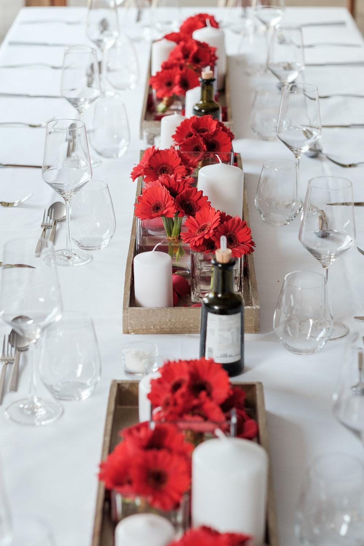 Sofie en Bernard hadden het privilege om in de tuin van de ouders van de bruidegom hun trouwfeest te houden. Geen slecht idee, zo bleek. De huwelijksfotografen van iso800 waren gelukkige getuigen. Sfeerbeeld van de tafel, gedekt met rode bloemen.