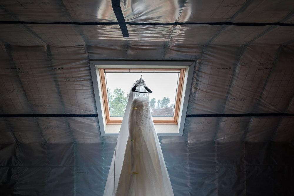 Een bruid met een geweer. Een fladderend trouwkleed in de Wase haven. Een koppel absolute lieverds met een schitterende openingsdans in Brebonna.  De huwelijksfotografen van iso800 stellen aan u voor: Linde en Tom. Sfeerbeeld van het trouwkleed dat klaarhangt op zolder.