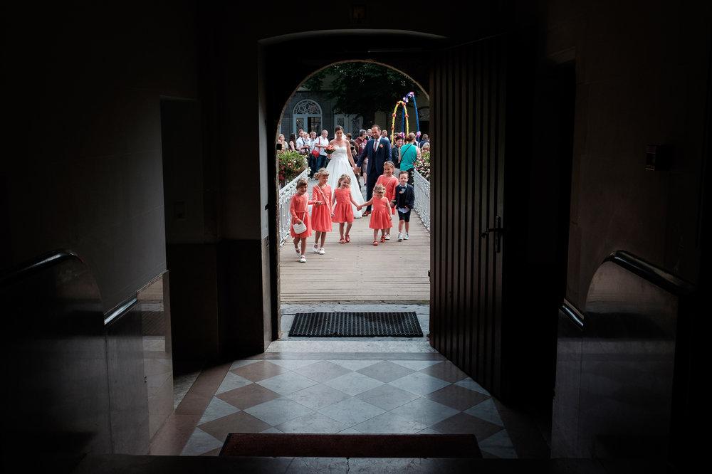 Een bruid met een geweer. Een fladderend trouwkleed in de Wase haven. Een koppel absolute lieverds met een schitterende openingsdans in Brebonna. De huwelijksfotografen van iso800 stellen aan u voor: Linde en Tom. Het bruidspaar en de bruidskinderen komen aan aan het gemeentehuis, Kasteel Cortewalle.