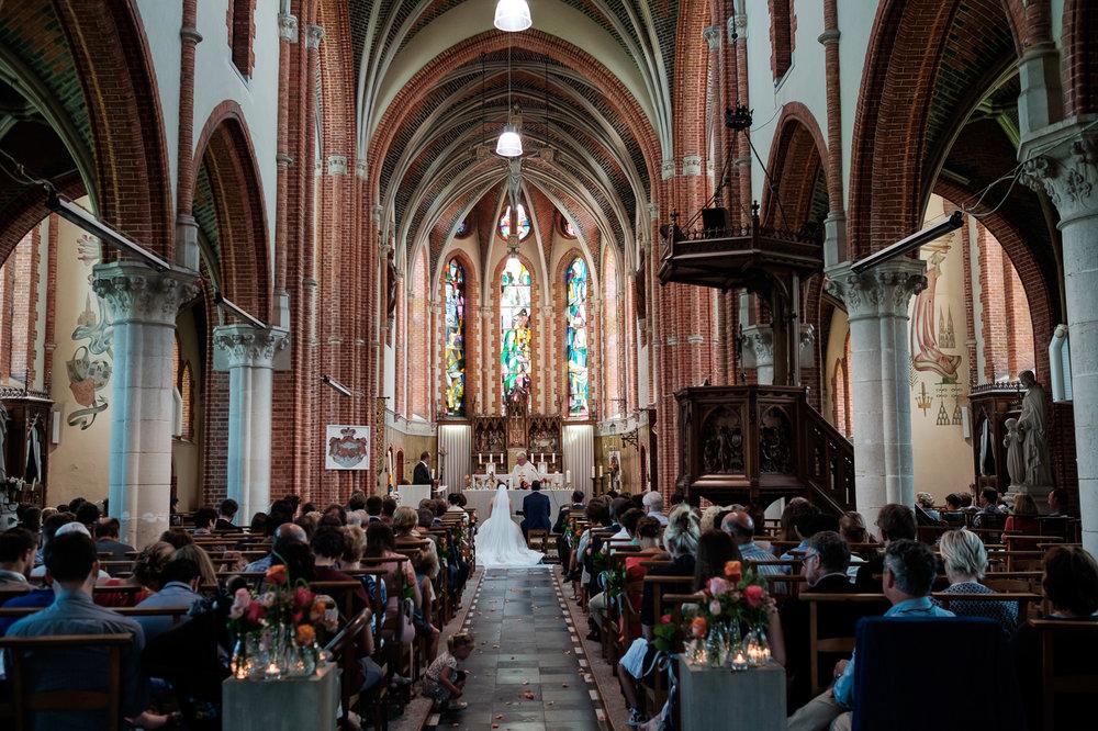 Een bruid met een geweer. Een fladderend trouwkleed in de Wase haven. Een koppel absolute lieverds met een schitterende openingsdans in Brebonna. De huwelijksfotografen van iso800 stellen aan u voor: Linde en Tom. Sfeerbeeld van de kerk tijdens de ceremonie.