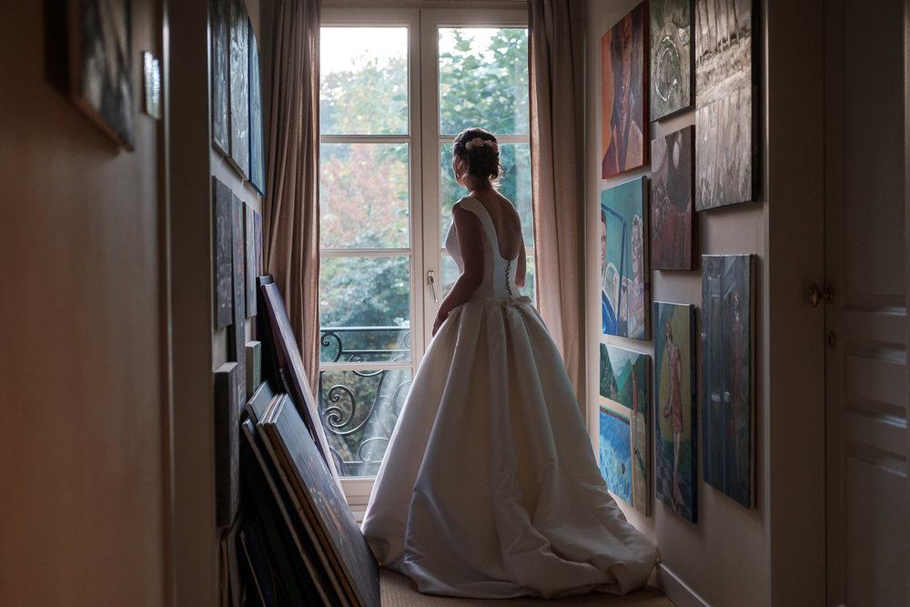 De huwelijksfotograaf van is800 was erbij toen   Camille en Francis elkaar  dit weekend het jawoord gaven. Kort samengevat zag dat er zo uit: Een huwelijk in de kathedraal (koor incluis), een feest in zaal Horta (need we say more), een bruid in prinsessenkleed (owning it all the way!), Een bruidegom die één en al stijl uitademt. De bruid kijkt door het raam in een kleine kamer vol schilderijen.