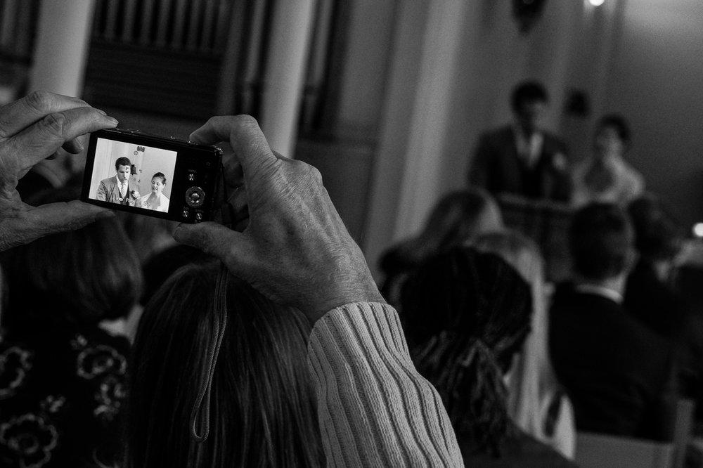 Britt & Jens zagen samen al de helft van de wereld, maar trouwen wilden ze graag in 'hun' Antwerpen.Met de huwelijksfotografen van iso800 trokken ze naar een pittoresk kerkje Lillo, vaarden met het prachtige zeilschip Marjorie II over de Schelde naar de voet van het MAS en gingen van daaruit het naar feestzaal LaRiva.Een man neemt een foto van het bruidspaar tijdens de ceremonie in de kerk.