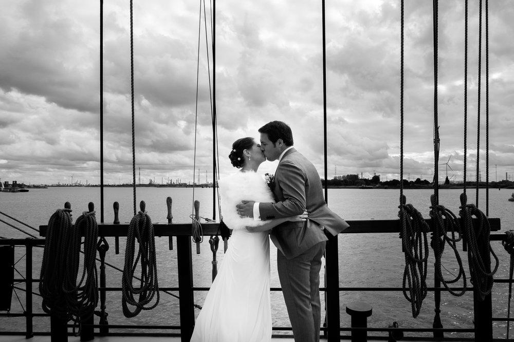 Britt & Jens zagen samen al de helft van de wereld, maar trouwen wilden ze graag in 'hun' Antwerpen.Met de huwelijksfotografen van iso800 trokken ze naar een pittoresk kerkje Lillo, vaarden met het prachtige zeilschip Marjorie II over de Schelde naar de voet van het MAS en gingen van daaruit het naar feestzaal LaRiva. Het bruidspaar zoent op de boot, met inde achtergrond de Antwerpse haven.