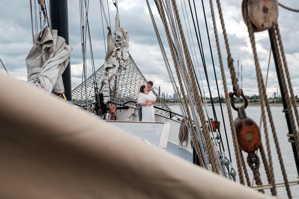 Britt & Jens zagen samen al de helft van de wereld, maar trouwen wilden ze graag in 'hun' Antwerpen.Met de huwelijksfotografen van iso800 trokken ze naar een pittoresk kerkje Lillo, vaarden met het prachtige zeilschip Marjorie II over de Schelde naar de voet van het MAS en gingen van daaruit het naar feestzaal LaRiva. Fotoshoot met het bruidspaar op het zeilschip.