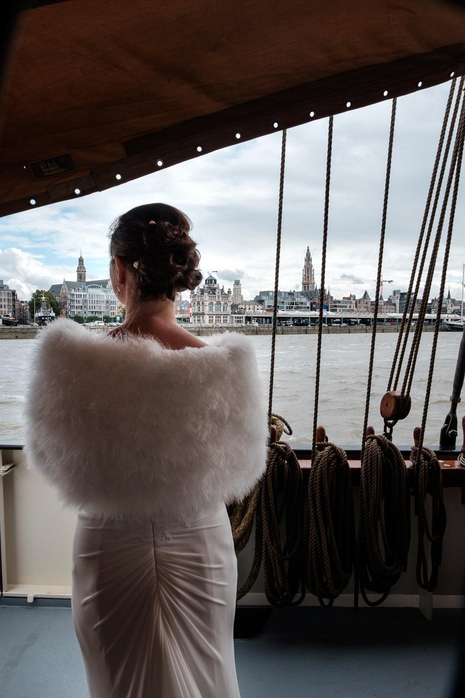 Britt & Jens zagen samen al de helft van de wereld, maar trouwen wilden ze graag in 'hun' Antwerpen.Met de huwelijksfotografen van iso800 trokken ze naar een pittoresk kerkje Lillo, vaarden met het prachtige zeilschip Marjorie II over de Schelde naar de voet van het MAS en gingen van daaruit het naar feestzaal LaRiva.Bruid kijkt toe hoe het schip aankomt in Antwerpen, met de Kathedraal en de boerentoren in de achtergrond.