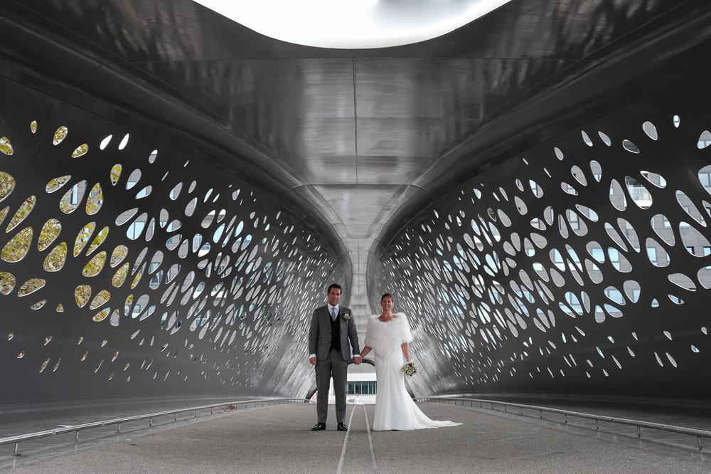 Britt & Jens zagen samen al de helft van de wereld, maar trouwen wilden ze graag in 'hun' Antwerpen.Met de huwelijksfotografen van iso800 trokken ze naar een pittoresk kerkje Lillo, vaarden met het prachtige zeilschip Marjorie II over de Schelde naar de voet van het MAS en gingen van daaruit het naar feestzaal LaRiva.Het bruidspaar op de nieuwe voetgangersbrug in Antwerpen Noord.