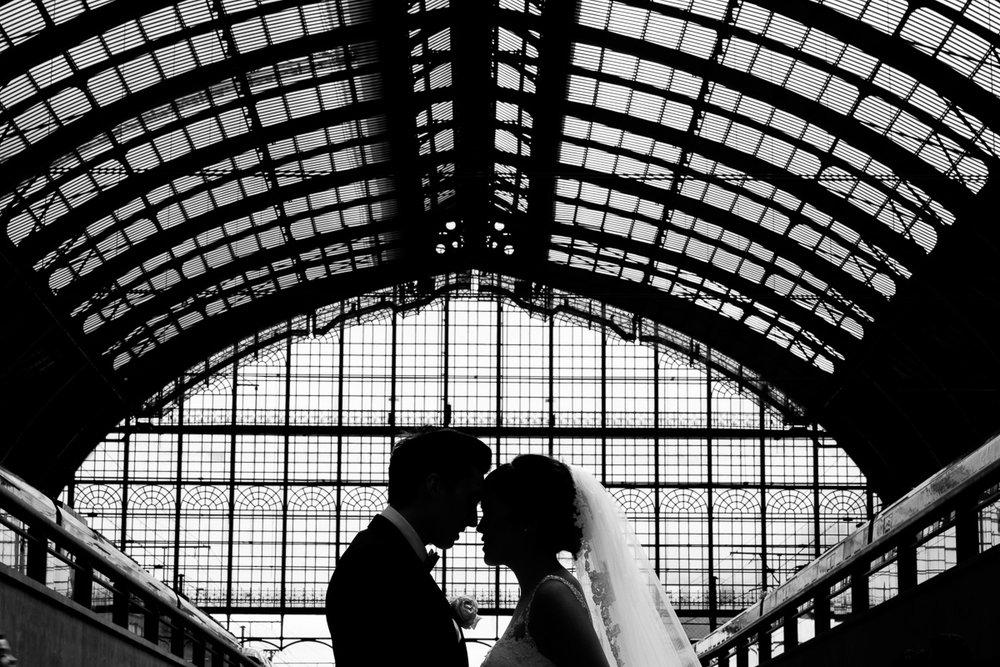 iso800 blikt terug op het voorbije jaar. In 2016 trokken de huwelijksfotografen en videografen van de Ardennen tot Toscane, van openingsdansen met fanfares tot heelder receptietafels in een zwembad. Een overzicht van de leukste beelden uit 2016. Zwartwitt foto van een bruidspaar tegen de magnifieke achtergrond van de koepen van het centraal station in Antwerpen.