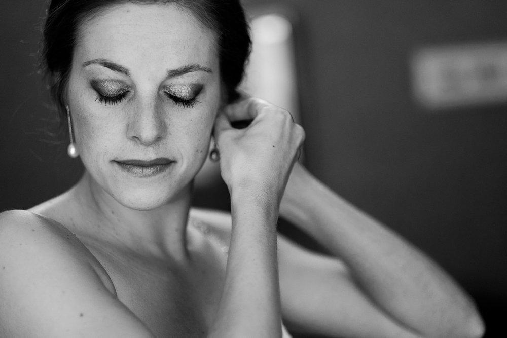 iso800 blikt terug op het voorbije jaar. In 2016 trokken de huwelijksfotografen en videografen van de Ardennen tot Toscane, van openingsdansen met fanfares tot heelder receptietafels in een zwembad. Een overzicht van de leukste beelden uit 2016. Zwartwit foto van bruid die zich opmaakt in de ochtend en haar oorbellen aandoet.