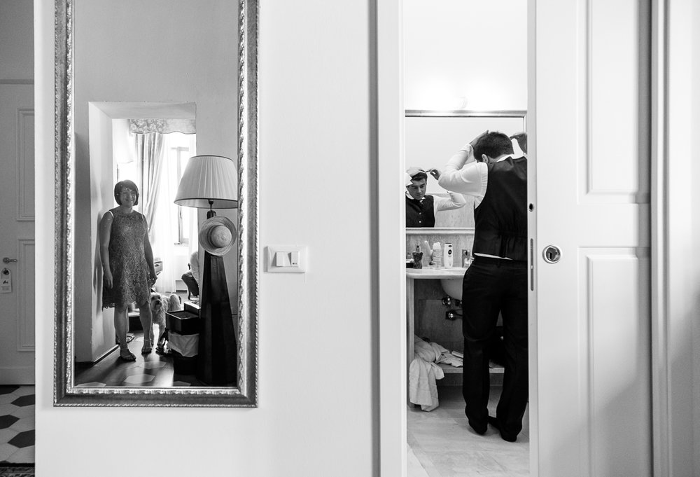 iso800 blikt terug op het voorbije jaar. In 2016 trokken de huwelijksfotografen en videografen van de Ardennen tot Toscane, van openingsdansen met fanfares tot heelder receptietafels in een zwembad. Een overzicht van de leukste beelden uit 2016. Zwartwit foto, bruidegom kamt zijn haren, in de spiegel zien we een vrouw en een hond toekijken.