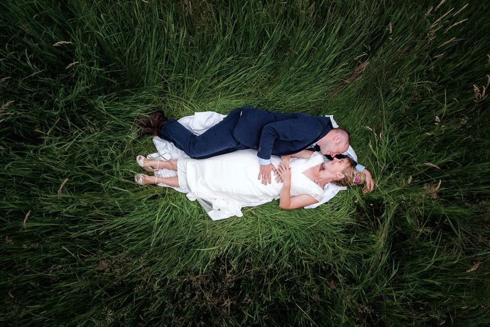 iso800 blikt terug op het voorbije jaar. In 2016 trokken de huwelijksfotografen en videografen van de Ardennen tot Toscane, van openingsdansen met fanfares tot heelder receptietafels in een zwembad. Een overzicht van de leukste beelden uit 2016. Het bruidspaar ligt in het hoge gras.