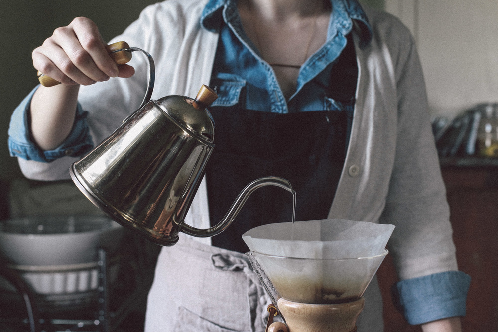Preparing coffee from start to finish is a delicious experience for the senses - grinding the beans, boiling the water, blooming your coffee grounds, and taking great care to produce the perfect cup. Rebecca is seen here wearing Consider The Wldflwr's bronze bar necklace.