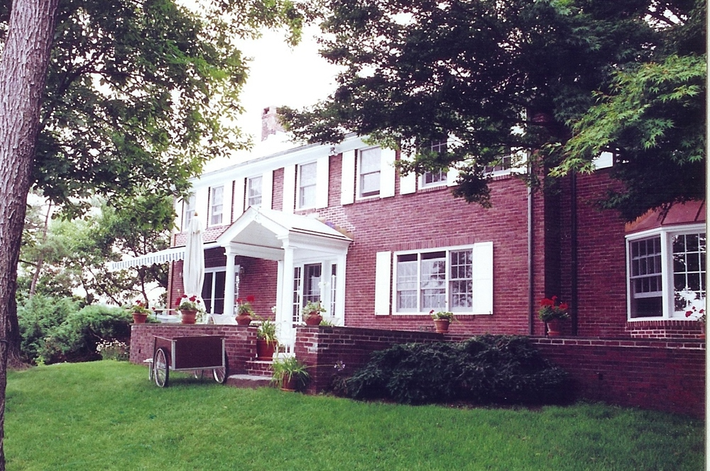 After - View of the south facade. Note the addition of a retractable awning, replacing the screened porch. Note the  new bay window in the living room, to the right.