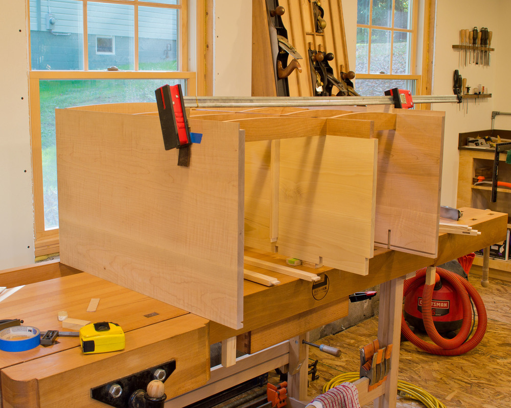 Assembling the horizontal dividers to the sides/vertical divider.  The horizontal divider is half-lapped at the vertical divider and has a dovetail tenon on each end that fits into dovetail mortises in the case sides.