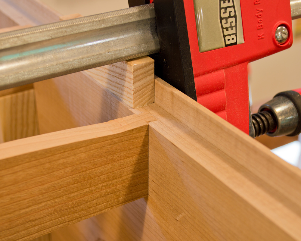 A little tough to make out, but you can kind of see the dovetail tenon on the end of the cherry horizontal divider (which has been inserted in the dovetail mortise on the case side).  There you have it, a sliding dovetail.