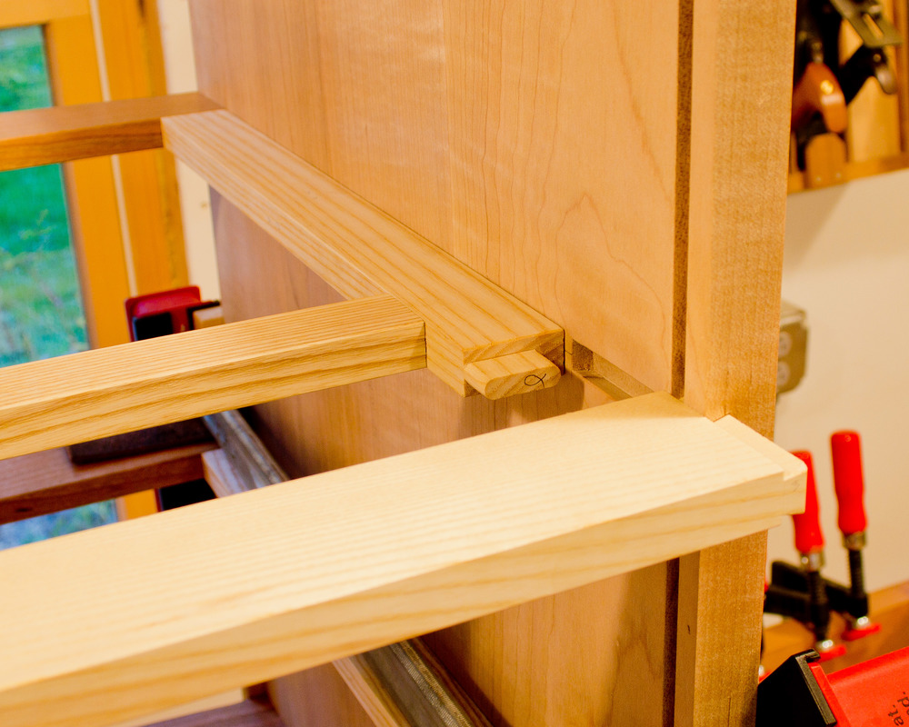 One of the rear horizontal dividers awaiting it's turn with the clamps.  You can see the tenon on the end of the runner, which fits into a corresponding mortise in the divider.