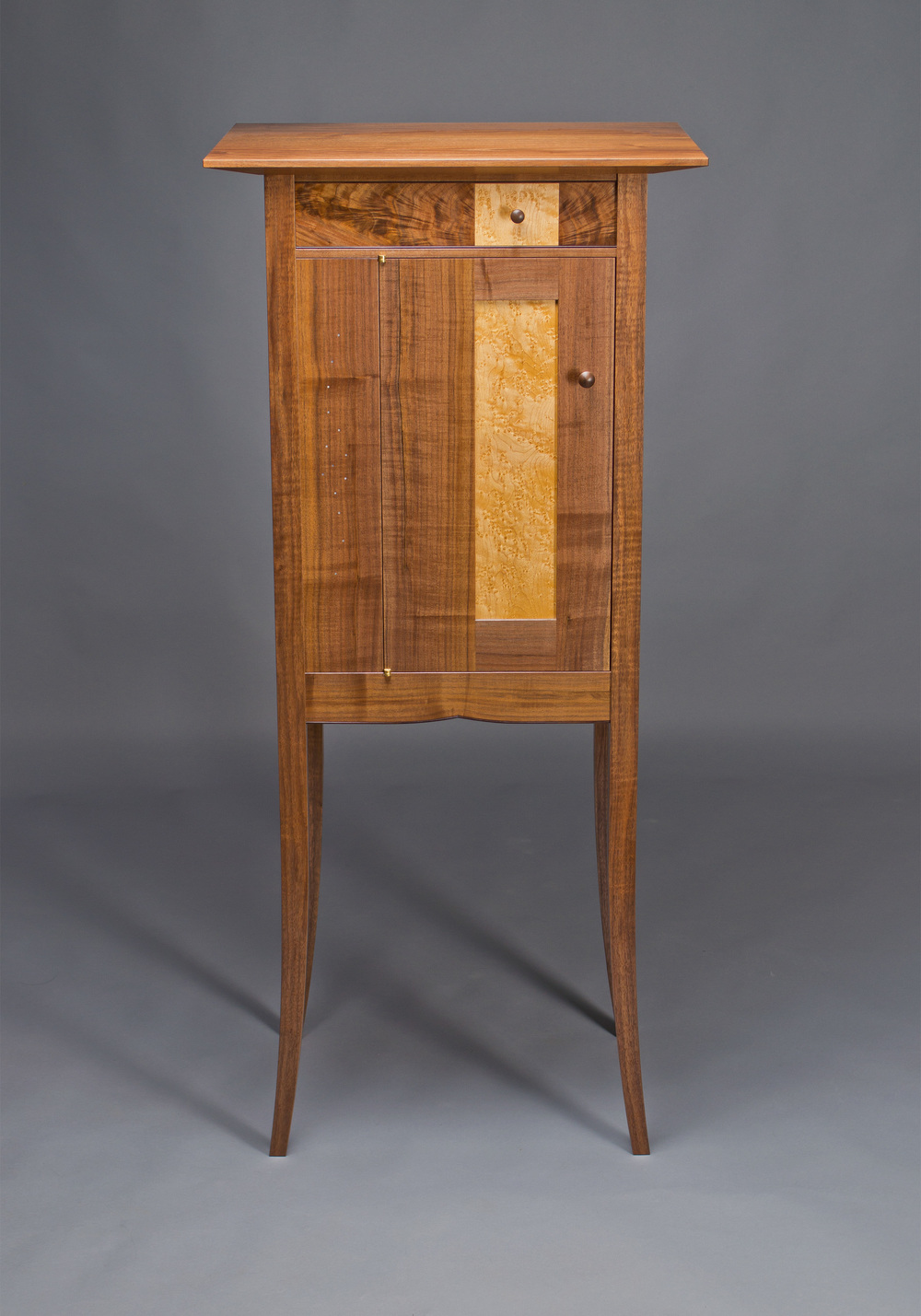 cabinet with curved legs made of black walnut and birds eye maple