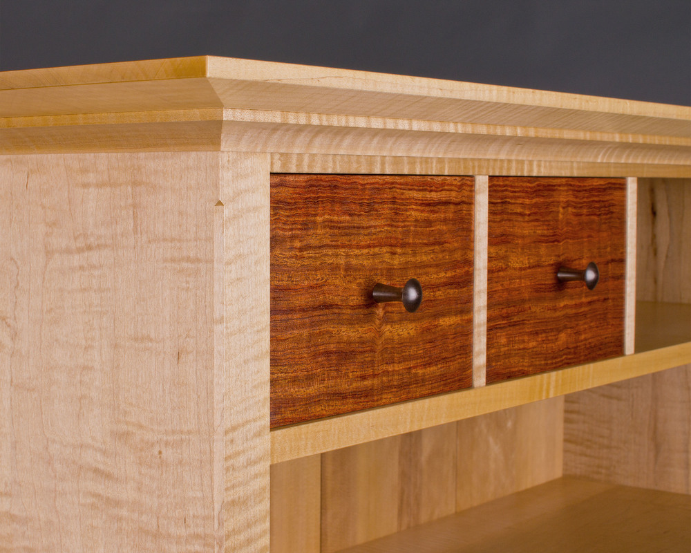 off-center drawer fronts are made of bubinga, with hand-turned rosewood knobs