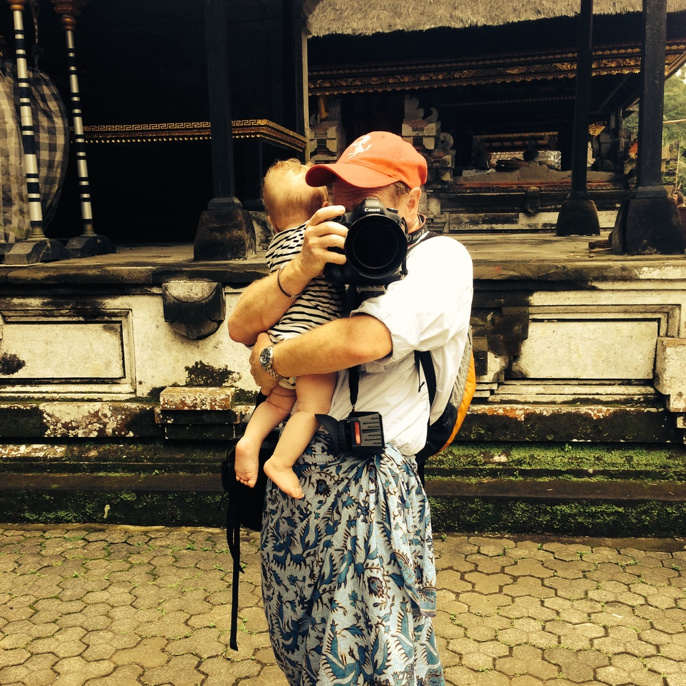 Multi-tasking Mr. Mom holding his 6 month old son at Tampaksiring temple in Bali, Indonesia