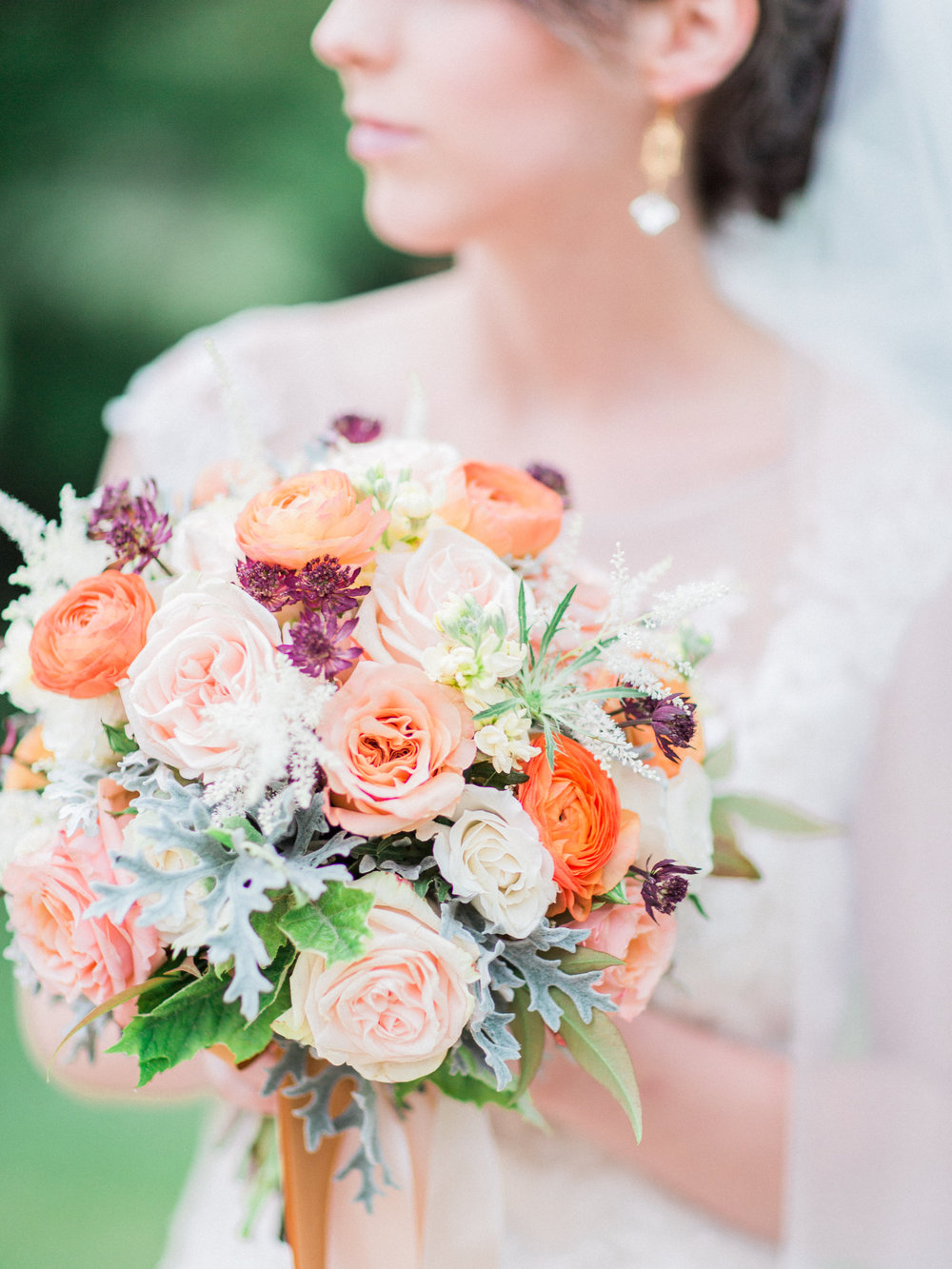 Bridal bouquet of peach Shimmer roses, orange ranunculus, purple astrantia by Lark Floral