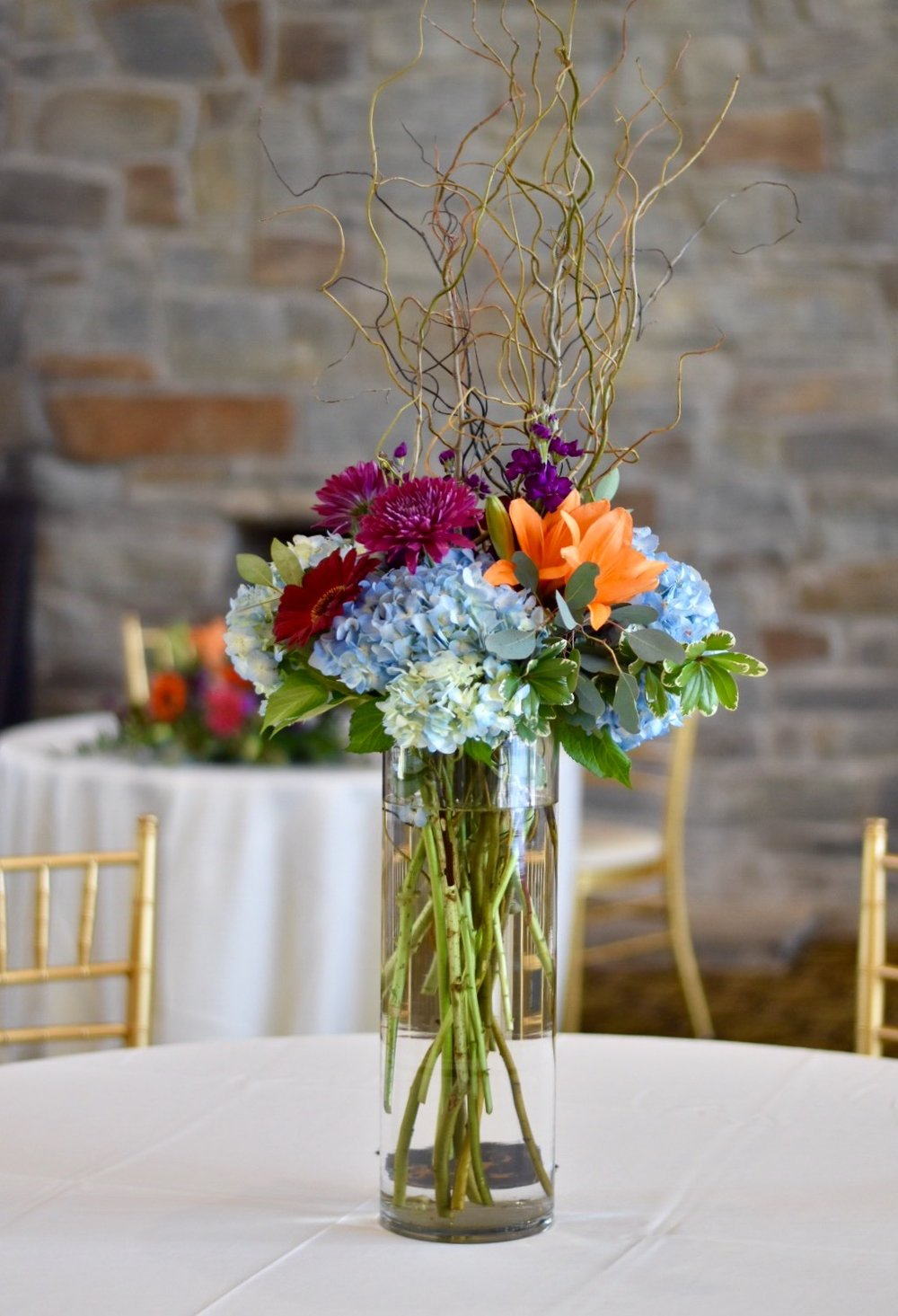 Tall centerpiece in glass cylinder with jewel toned flowers by Lark Floral