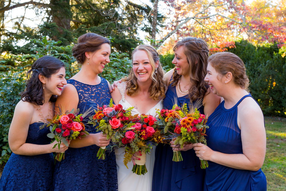 Bridesmaids in navy blue with orange flowers