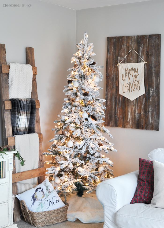 Flocked Christmas tree decorated with all white ornaments & pinecones {Christmas Tree Inspiration Roundup} - Stevie Storck Design Co.