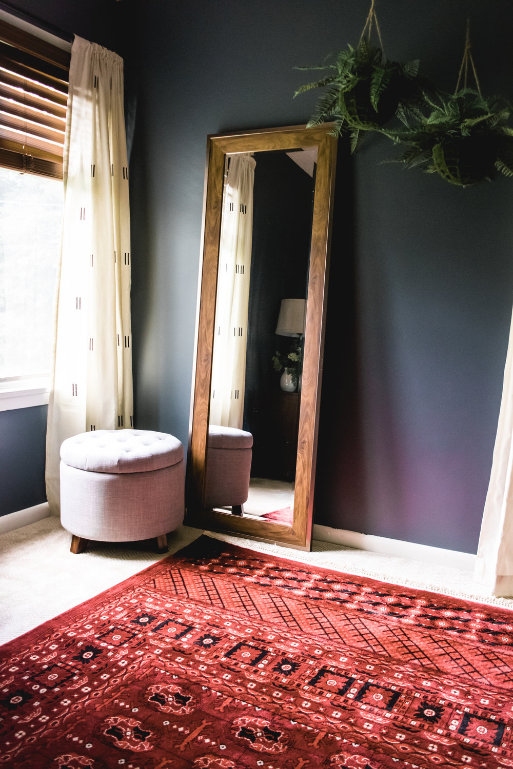 dark moody bedroom design | sherwin williams grays harbor, antique metal bed, affordable persian rug, red persian rug, leaning floor mirror, hanging ferns