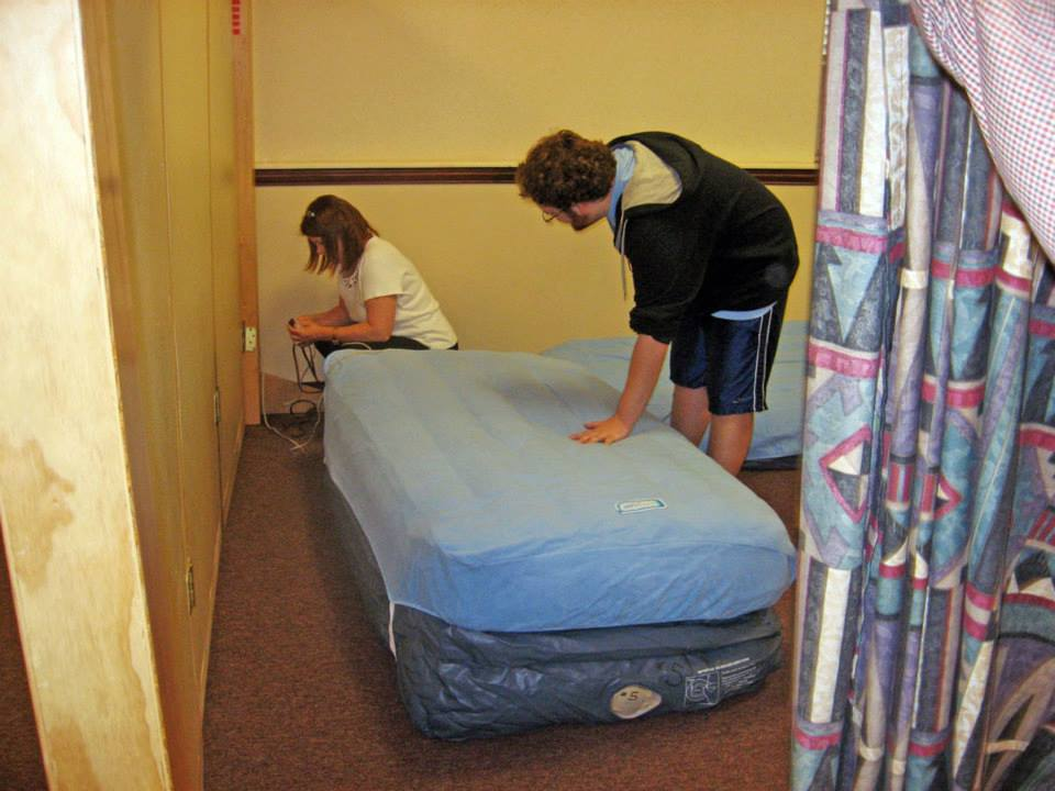 Volunteers set up beds for IHN guests
