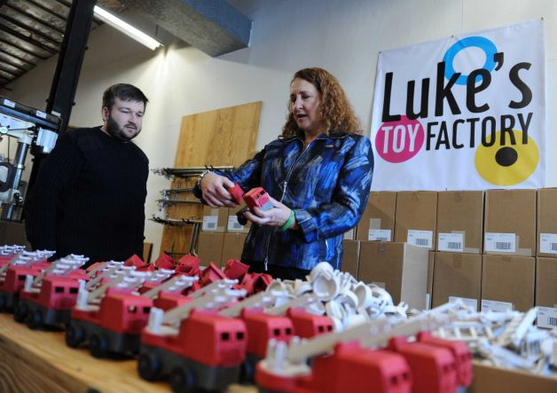 Luke shows U.S. Congresswoman Esty how his firetrucks are assembled
