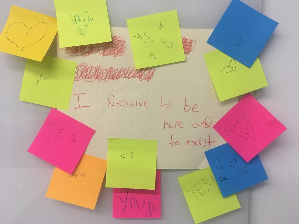 """""""I deserve to be here and to exist."""" Anonymous student statement taped on the wall during in-class workshop in RHE 678C: Writing Center Internship in spring 2018. Sticky notes pasted on the statement are anonymous responses from fellow students."""