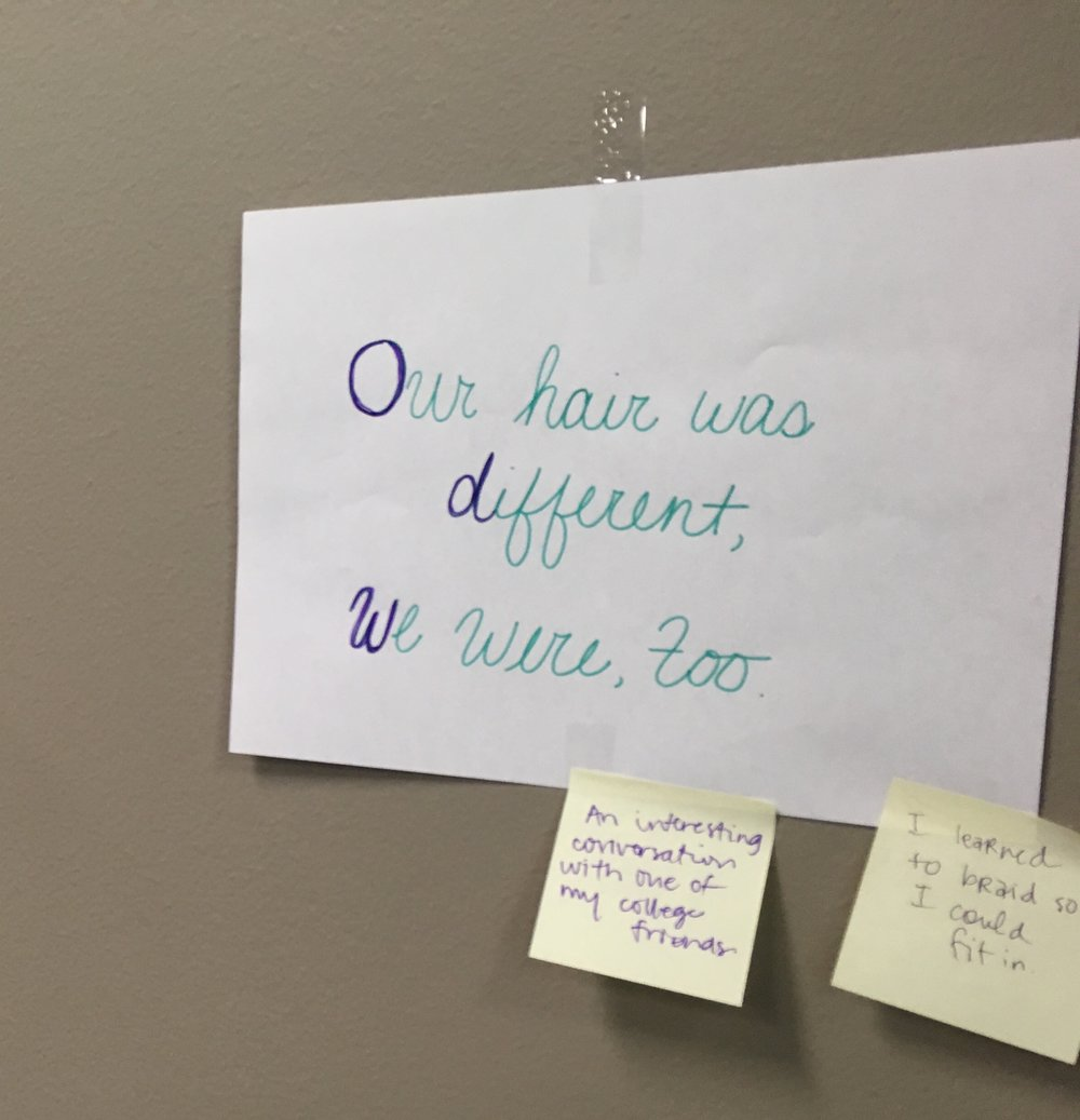 """""""Our hair was different, we were, too.""""Anonymous participant statement taped on the wall during Natasha Tinsley et al.'s workshop at 2018 SCWCA. Sticky notes pasted on the statement are anonymous responses from fellow participants."""
