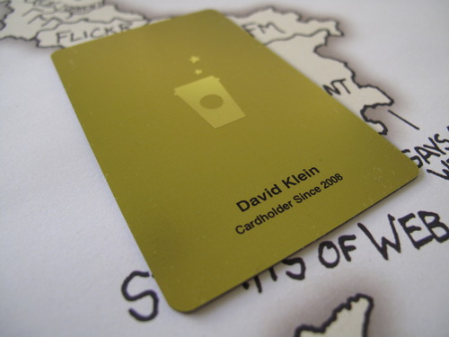 """New Starbucks Gold Card: Well, the Starbucks Gold Card is finally… gold. The best part though is my name being printed on it. Awesome. This was mailed to me along with the details of the new program. Free drink """"just for being gold."""" Free drink on my birthday. 2 hours of wi-fi every day. Free refills on coffee. Free syrups. Free soymilk (apparently they charge more?) Free coffee every time I purchase a pound of beans (which I do - Pike Place Roast) Exclusive offers & coupons (this is serious - Starbucks once put $10 on the card for no reason) Free drink every 15 stars (you get a star each time you buy a drink) My only concern is I don't see anything about my usual 10% off everything deal. Uh oh. Note: This photo required macro mode to achieve legible text. Also, underneath is the XKCD Online Communities Poster."""