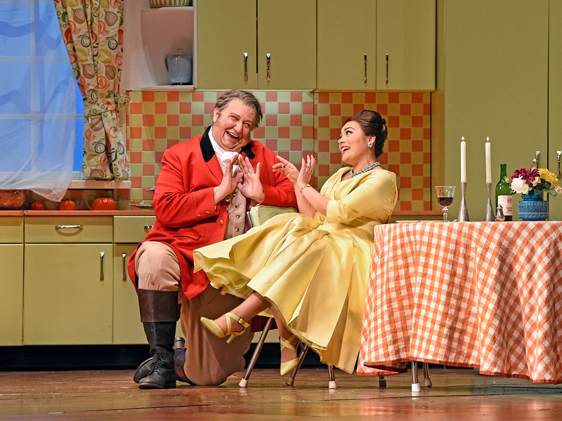 Falstaff courts Alice Ford in her modern kitchen in Scene IV of Act I