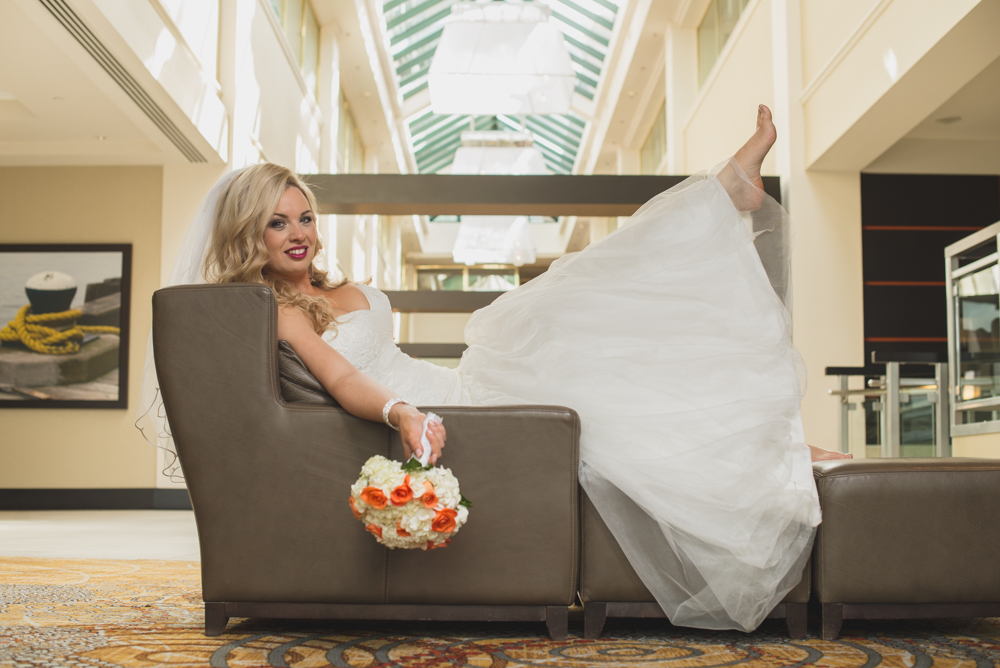 A blonde bride posing for a photo with her bouquet in hand while sitting on a chair. This is a wedding photograph taken by One Blue Fish Photography at the Halifax Harbourfront Marriott