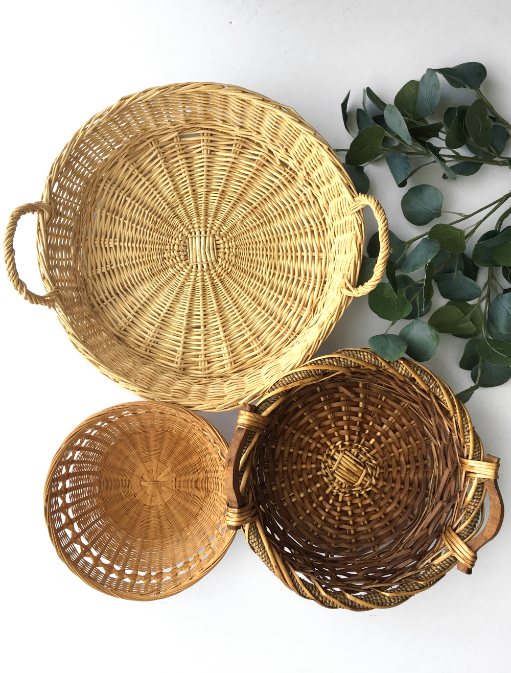 "Group of decorative natural baskets in various sizes. Large measures 16.5"" wide and 5.5"" deep (including handles). Dark basket measures 13"" wide (including handles) and 4.5"" deep. Small basket is 9.5"" wide and 3.5"" deep."