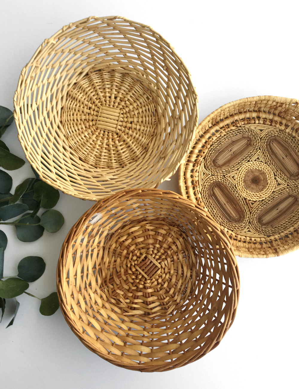 "Group of decorative baskets perfect for boho wall decor. Made of natural materials - all measure around 12"" wide. Two baskets are 4"" deep and more intricate basket is 2.5"" deep."