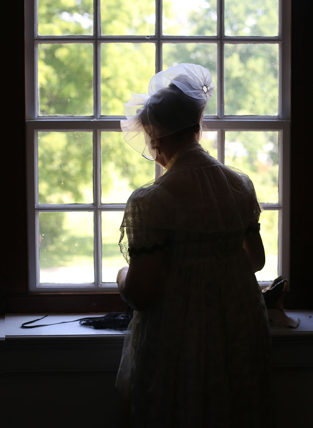 an interpreter uses the natural light to do some last minute stitches at locust grove in louisville, ky during the 10th annual jane austen festival.