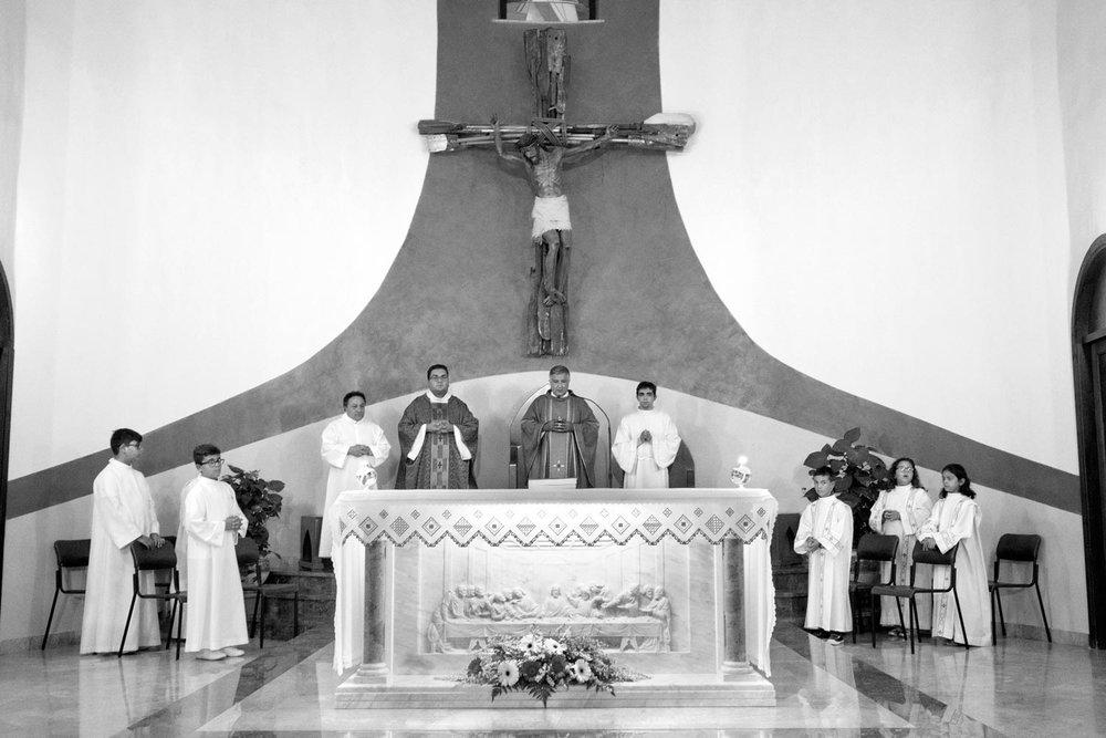 Don Mimmo Zambito celebra la Messa domenicale alla parrocchia di San Gerlando a Lampedusa. Sulla parete il crocifisso di un artista cubano donato da Papa Francesco alla parrocchia.
