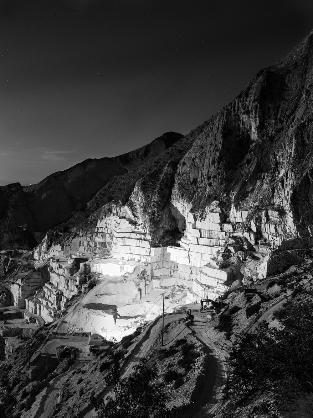 "One of the marble quarries in the Fantiscritti basin, behind the city of Carrara. The basins are inside the protected area of Alpi Apuane, which are defined ""Alps"" due to their morphology and are a mountain system that goes from the north-west of Tuscany and spreads over a surface of 400 square km. The mountains are formed by a dorsal which runs parallel to the Tirrenian coast and raises up to 2000 meters. In Carrara 18 torrents separate about 200 marble quarries. The landscape is huge and surreal.