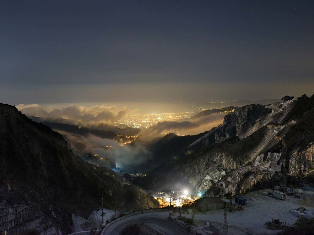 A view of the lower part of Fantiscritti marble basin in the evening, when the wind blows the air from the mountains to the valley of Carrara. The city stands between the Mediterranean sea and the Apuan Alps. The city has about 60 thousand citizens. Because the mountains have been privatized many years ago, very little or none of the income from the marble quarries is redistributed to the city public administration.