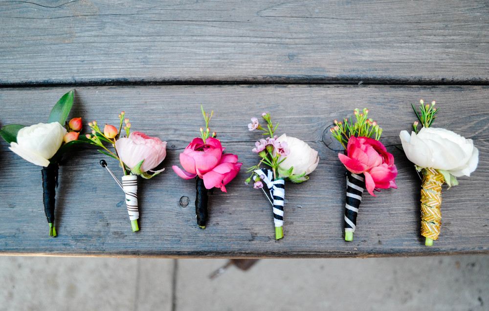 Pink, white, and red boutineers with mismatched black, gold, and navy blue striped ribbons!  Rosehip Social, Brooklyn, NY.