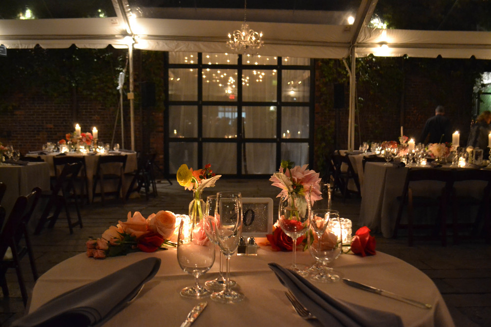 Candlelit centerpieces with pillar candles and pink and peach toned flowers. Foundry LIC. Rosehip Social.