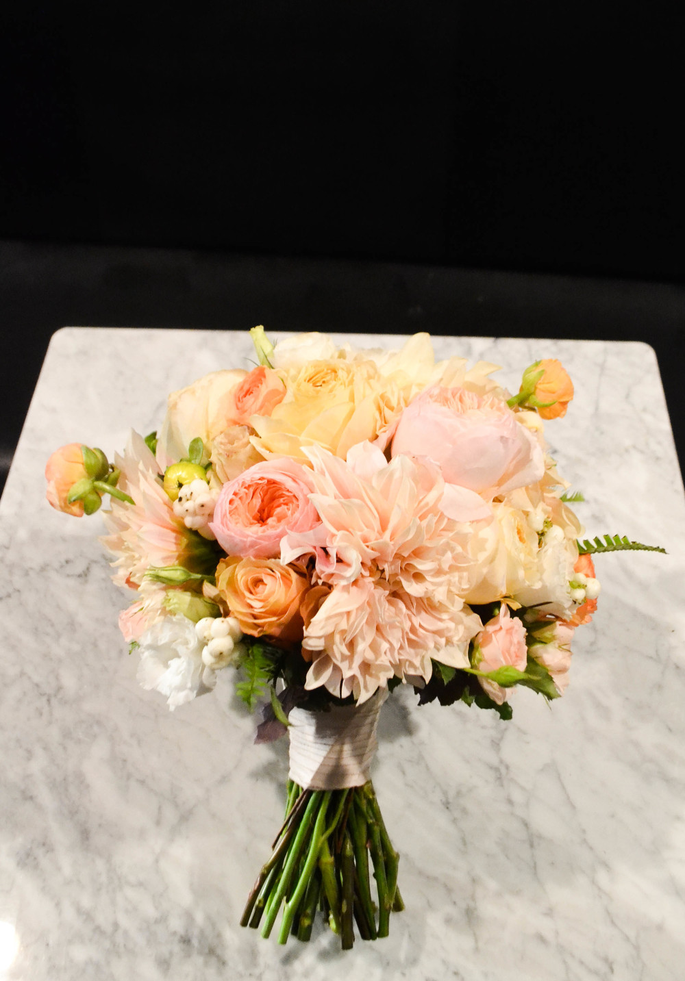 Bridal bouquet including cafe au lait dahlias, garden roses, sahara rose, spray rose and ranunkulous. Lush round classic bouquet with faded fall colors. Gramercy Park Hotel Terrace Wedding. Rosehip Social Floral Design.