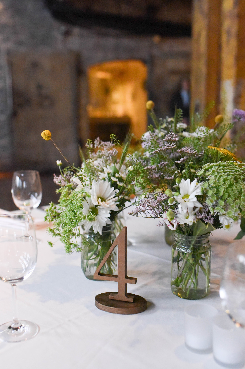 Yellow and lavender Wildflower centerpiece in rustic mason jar. Pale yellow, lavender, blush pink and orange flowers. Underrated and beautiful flowers. Greenpoint Loft wedding, Brooklyn. Flowers by Rosehip Social, Graham Ave, Brooklyn.