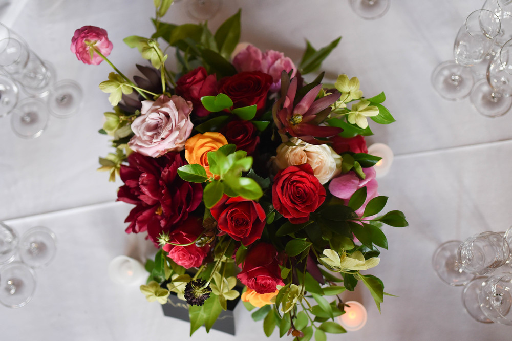 Lush center piece of romantic blooms. Flowers include peonies, roses and bright greens. Deep romantic red tones accompanied by a pop of orange.
