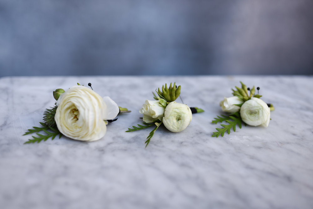 501 Union wedding boutonnieres. White ranunculus and greenery accents.
