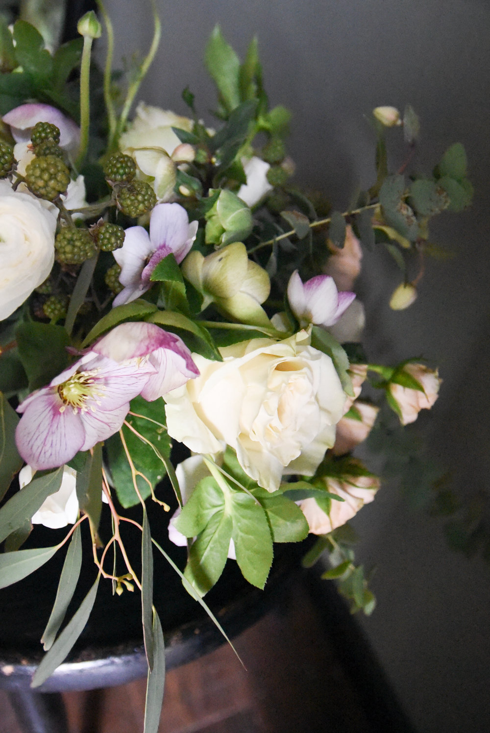 A combination of purple clematis, white roses, eucalyptus and berries feels so natural