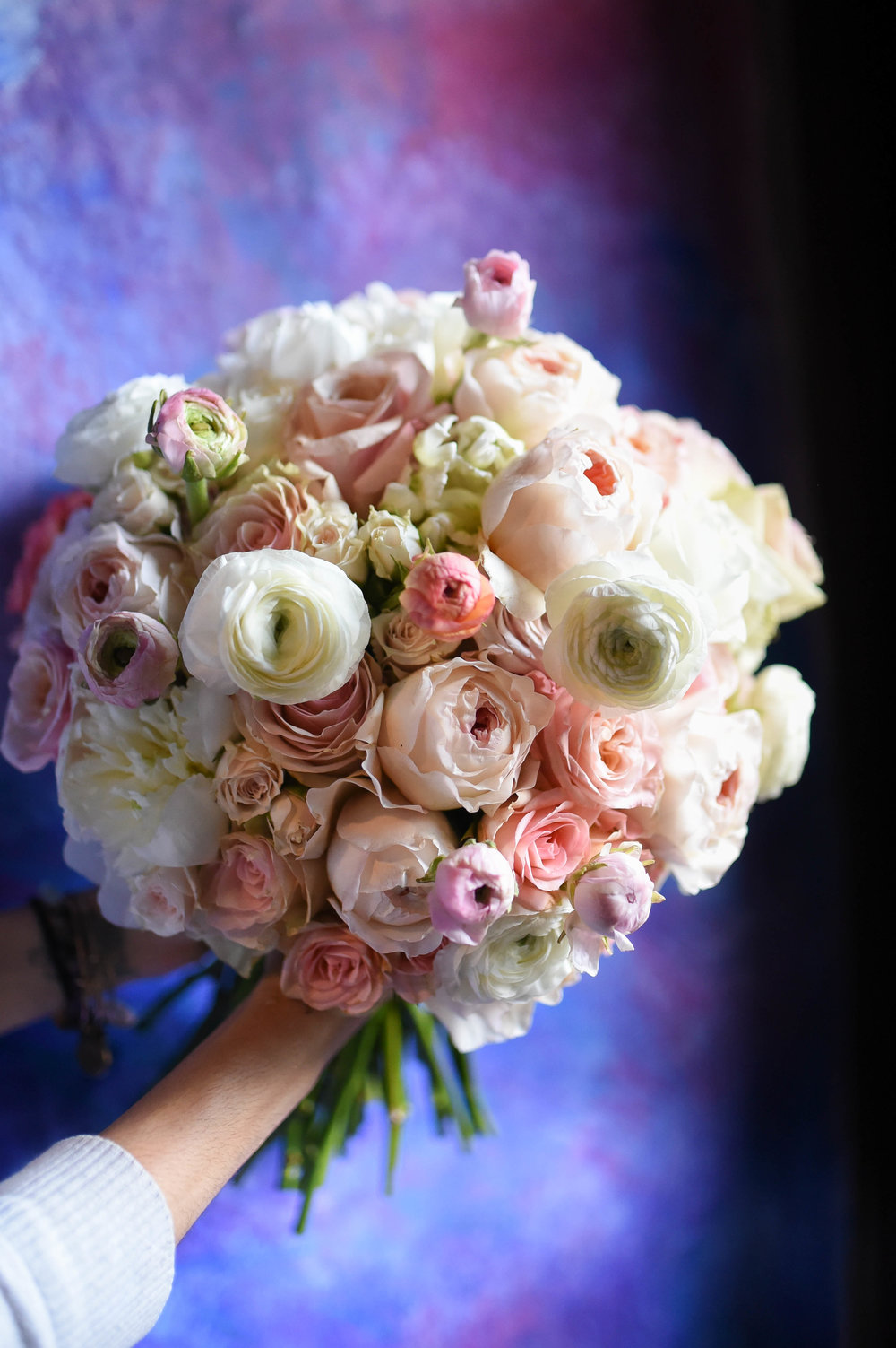 The monumental bridal bouquet is filled with soft pink and white blooms